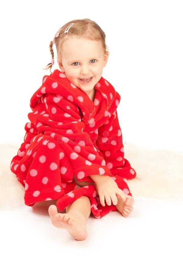 Menina no dressing-gown vermelho que senta-se no assoalho fotografia de stock royalty free