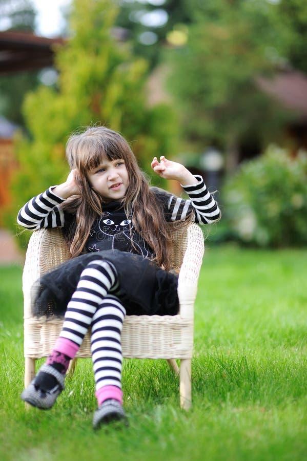 A menina no equipamento de Halloween mostra no jardim fotografia de stock