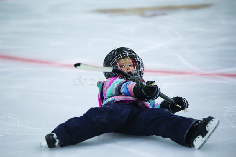Menina no equipamento do hóquei que cai para baixo na pista de gelo imagens de stock