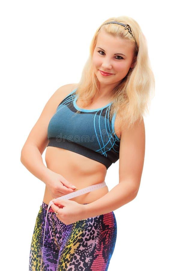 Menina no equipamento dos esportes que mede sua cintura foto de stock