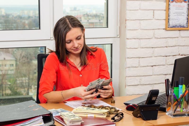 A menina no escritório conta o dinheiro, sentando-se na tabela imagens de stock