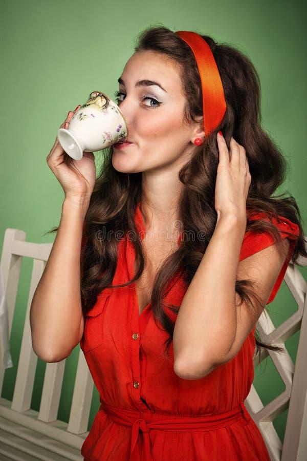 A menina no estilo retro bebe o chá fotografia de stock