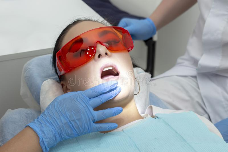 Menina no exame no tratamento do dentista do dente cariado o doutor usa um espelho no punho e em uma máquina do boro fotos de stock