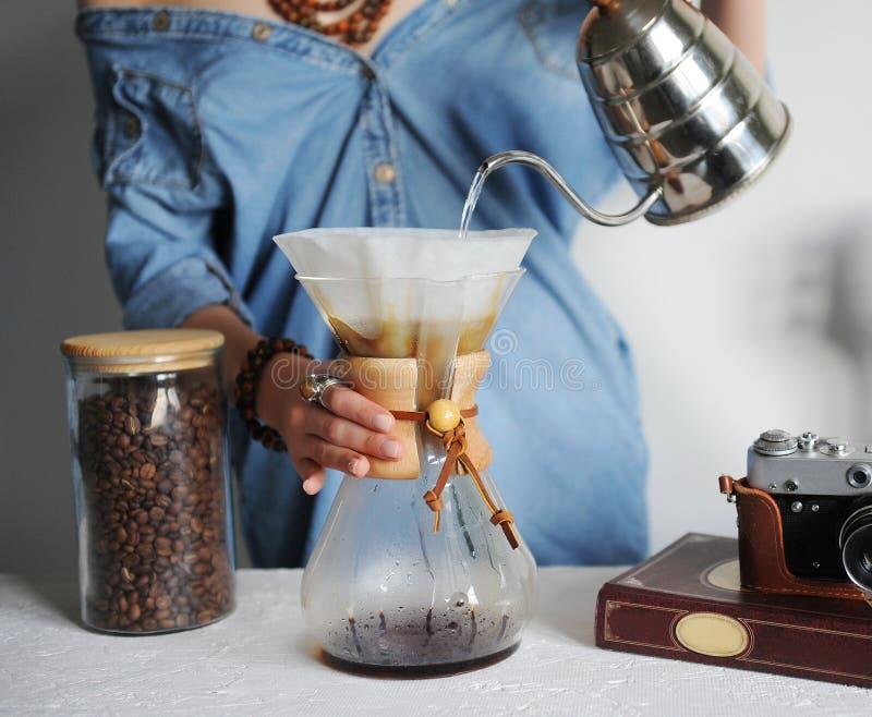 Menina no filtro de café alternativo das fermentações da camisa da sarja de Nimes Derrama a água da chaleira do nariz do ganso Cl fotografia de stock royalty free