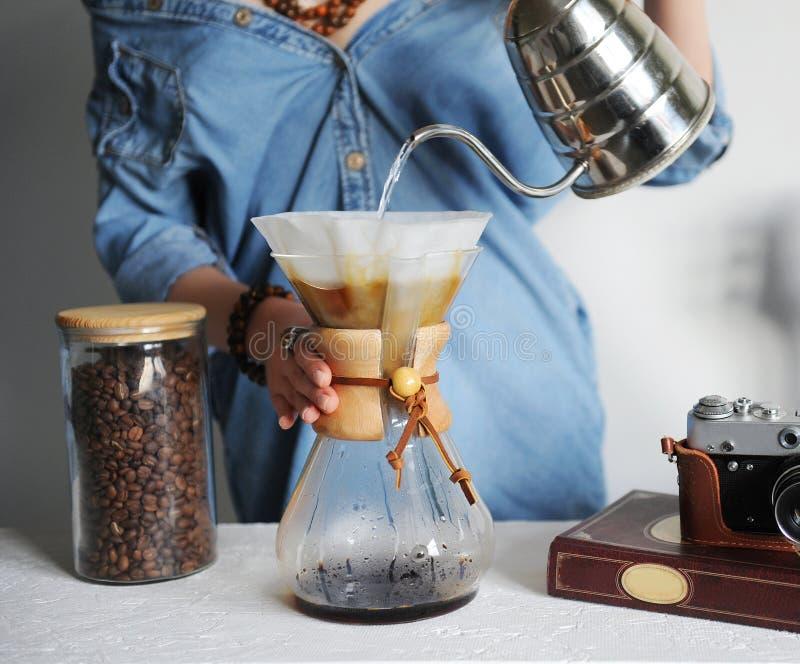 Menina no filtro de café alternativo das fermentações da camisa da sarja de Nimes Derrama a água da chaleira do nariz do ganso Cl imagens de stock royalty free