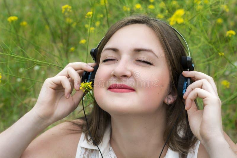Menina no fones de ouvido na natureza imagem de stock