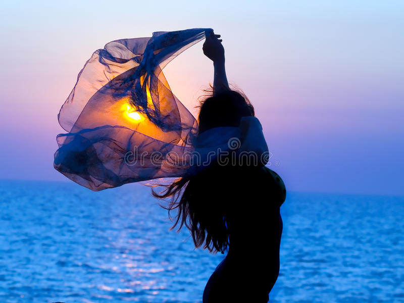 Menina no fundo do por do sol. imagens de stock royalty free