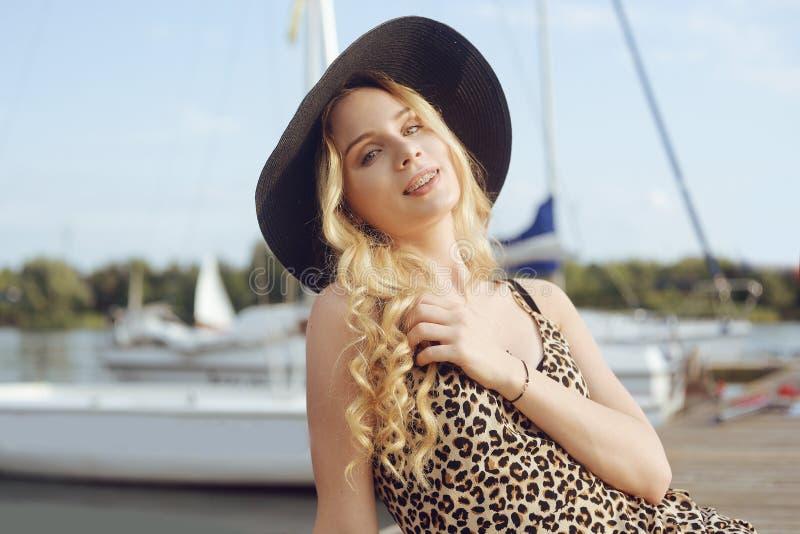 Menina no fundo dos iate, sorriso dos barcos de navigação Um louro bonito está sentando-se no cais, em um vestido com um leopardo imagens de stock
