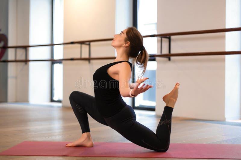 A menina no gym faz a ioga para manter-se na forma ou no peso adicional do controle imagem de stock
