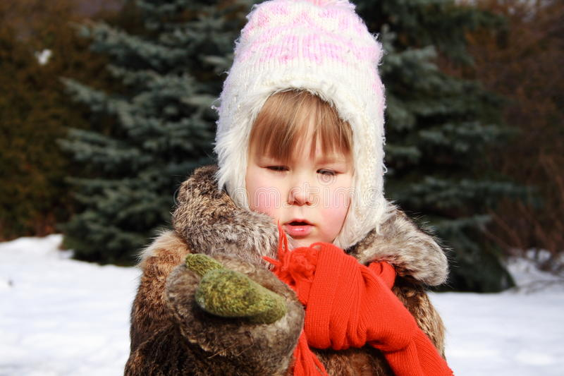 Menina no inverno que prende um floco de neve foto de stock