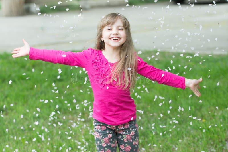 Menina no jogo da grama verde com as pétalas da flor na mola foto de stock royalty free