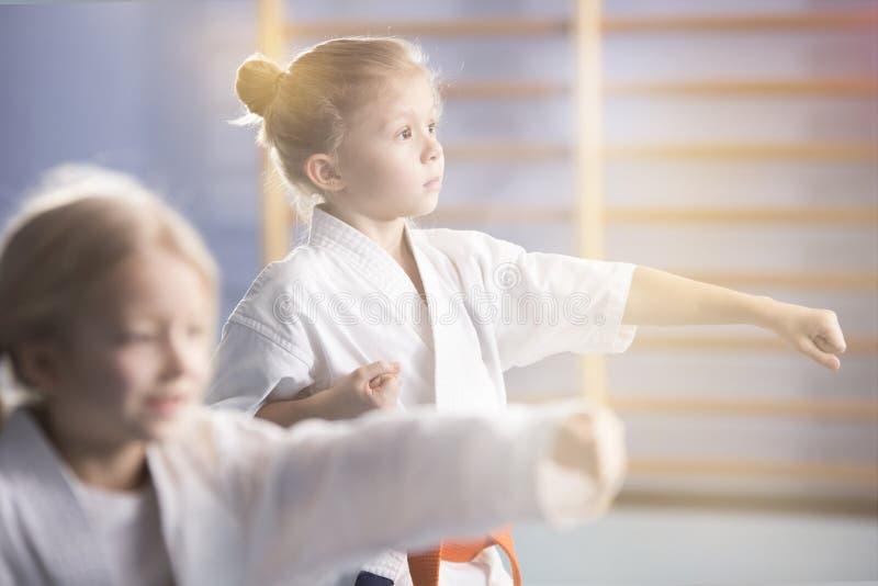 Menina no karaté praticando do quimono fotos de stock