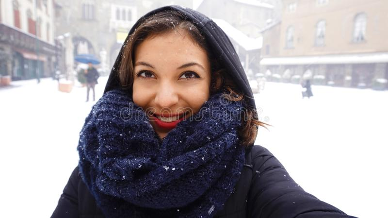 A menina no lenço morno e o tampão tomam o autorretrato na neve do inverno velha imagem de stock