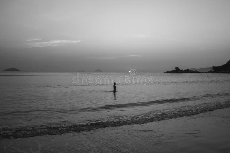 Menina no litoral no fundo do nascer do sol e do por do sol imagens de stock royalty free