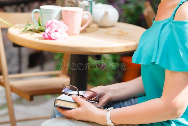 Menina no livro de leitura do restaurante do caffe imagem de stock