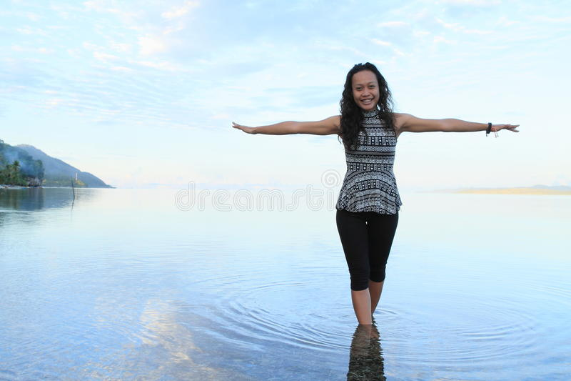 Download Menina No Mar Do Nascer Do Sol Foto de Stock - Imagem de tropics, sorriso: 65576672