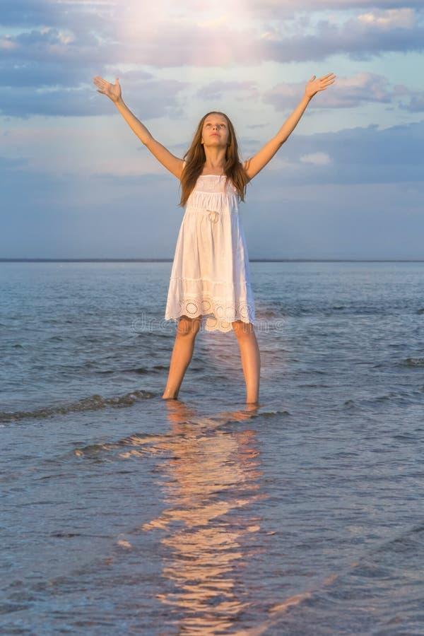 A menina no mar no por do sol diz adeus ao sol imagens de stock royalty free