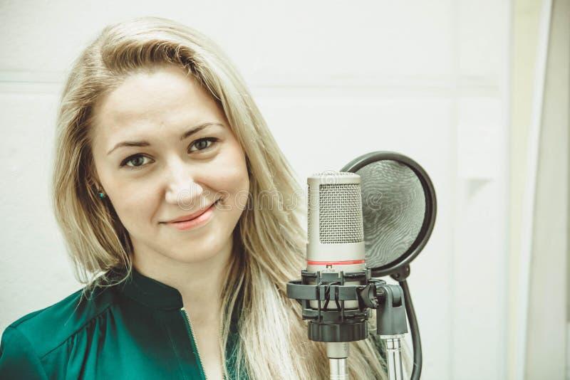 A menina no microfone no estúdio fotos de stock