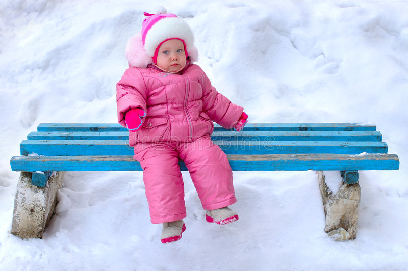 A menina no outerwear do inverno senta-se no banco. imagem de stock