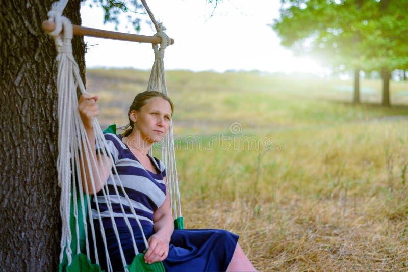 A menina no parque é de descanso e de assento em uma rede, na perspectiva do sol de nivelamento e da vista na distância foto de stock royalty free