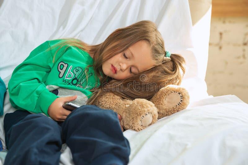 Menina no pijama suave e quente jogando em casa foto de stock