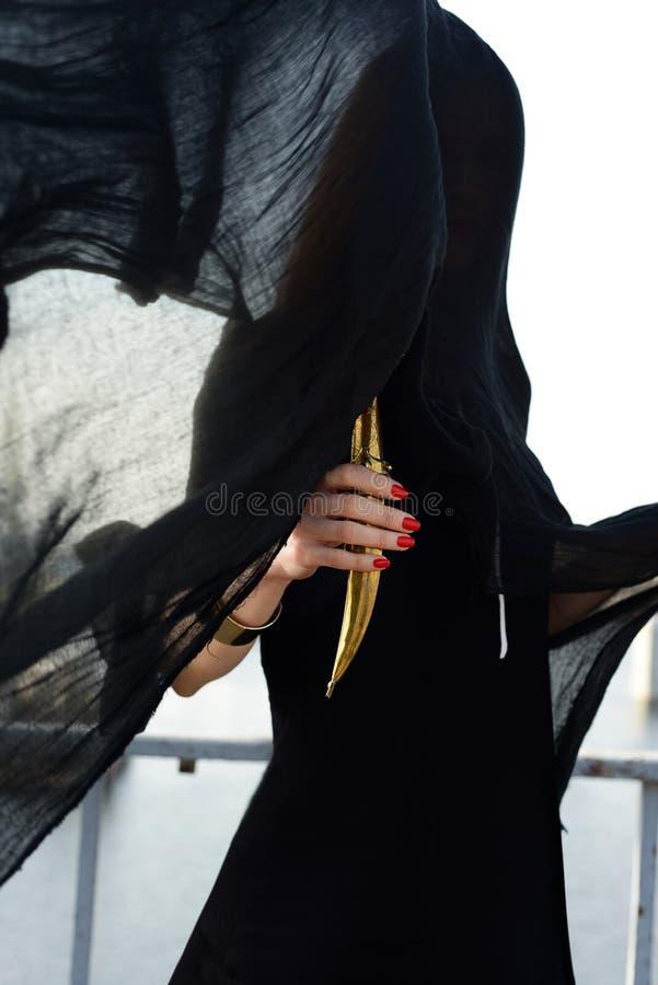 Menina no preto com um punhal oriental foto de stock royalty free