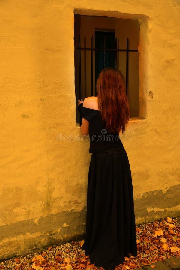Menina no preto em uma janela imagens de stock royalty free