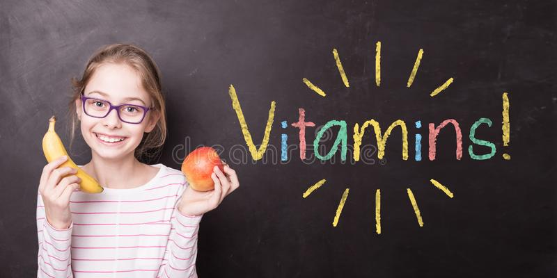 Menina no quadro com frutos e 'vitaminas! 'sinal imagens de stock