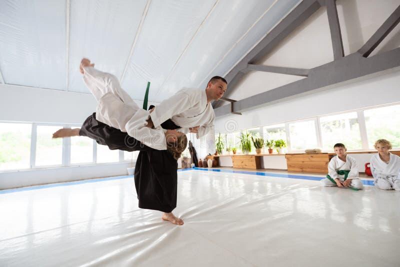 Menina no quimono branco que tem a luta com seu instrutor fotos de stock royalty free
