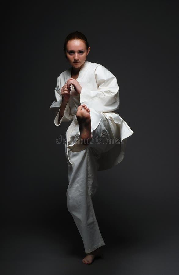 A menina no quimono branco retrocede o pé esquerdo para diante imagens de stock royalty free