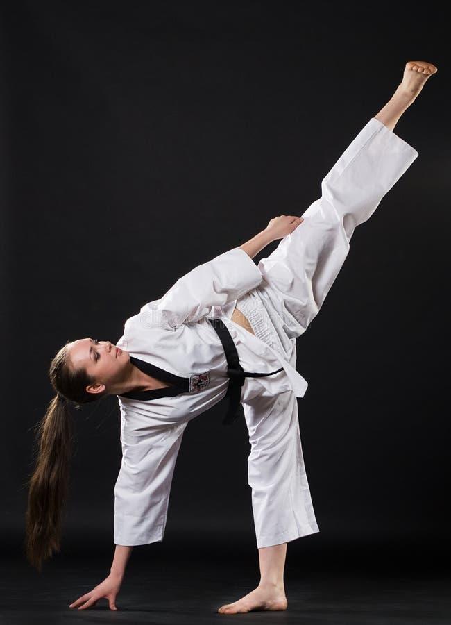 Menina no quimono que exercita o kata do karaté imagem de stock