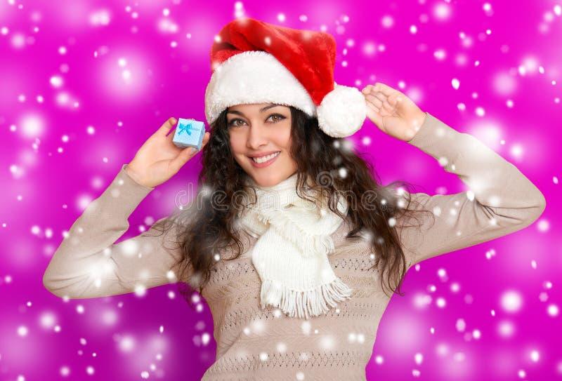 Menina no retrato do chapéu de Santa com pouca caixa de presente que levanta no fundo da cor, no conceito do feriado do Natal, em imagem de stock royalty free