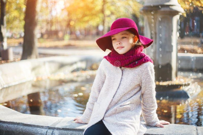 Menina no revestimento e no chapéu clássicos no parque do outono perto da fonte Estação do outono, forma, infância fotos de stock