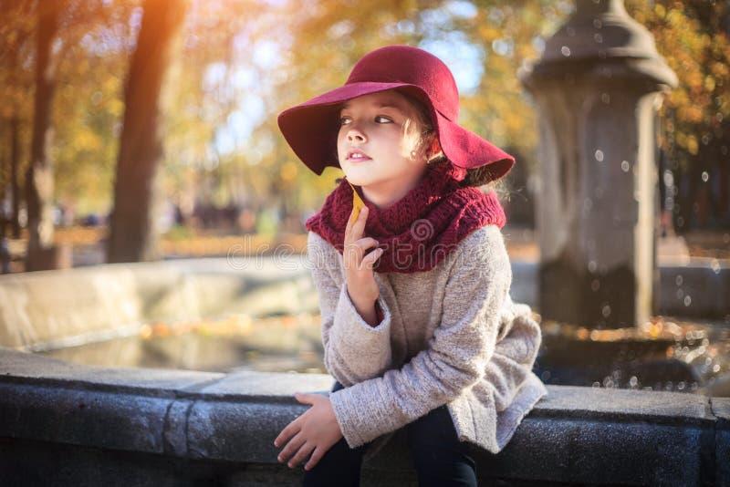 Menina no revestimento e no chapéu clássicos no parque do outono perto da fonte Estação do outono, forma, infância imagens de stock royalty free