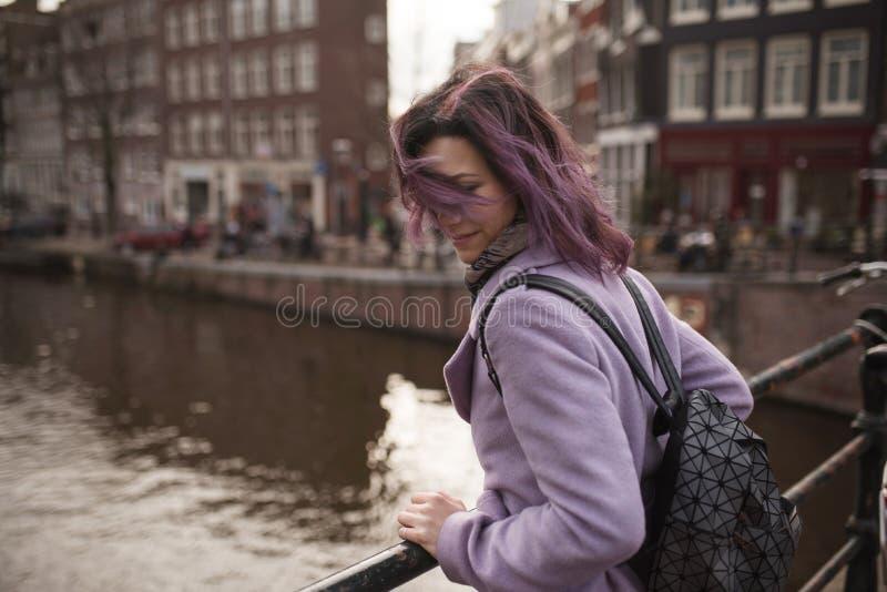 Menina no revestimento e na trouxa que aprecia a cidade de Amsterdão Jovem mulher que olha ao lado no canal de Amsterdão fotografia de stock royalty free