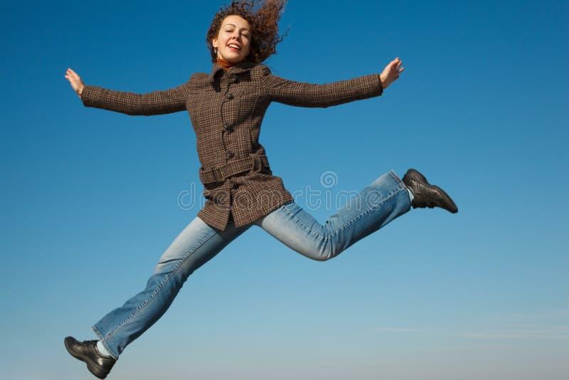 Menina no revestimento e nas calças de brim no salto de encontro ao céu azul fotografia de stock royalty free