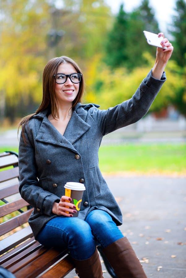 A menina no revestimento faz a foto do selfie, sentando-se em um banco com vidros, guardando o café ou o chá, outdoo novo imagem de stock royalty free