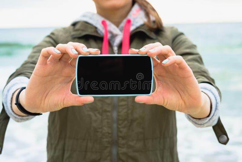 A menina no revestimento verde mostra uma tela vazia do telefone em um fundo foto de stock royalty free