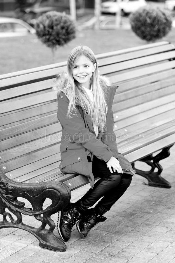 A menina no revestimento vermelho senta-se no banco no parque fotografia de stock