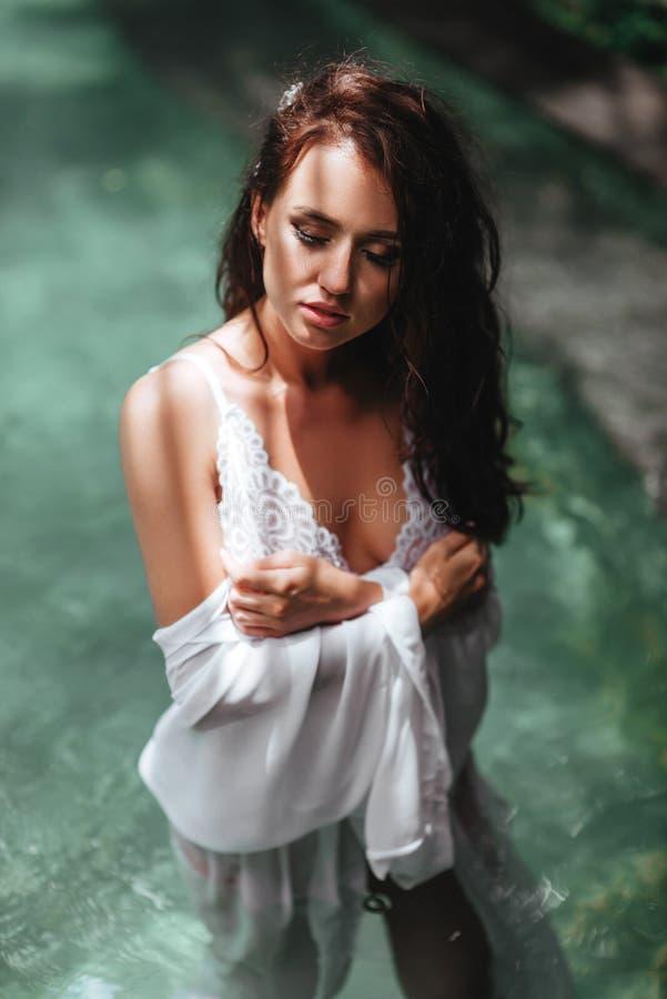 Menina no roupa de banho verde que refrigera para fora perto da piscina privada imagem de stock royalty free