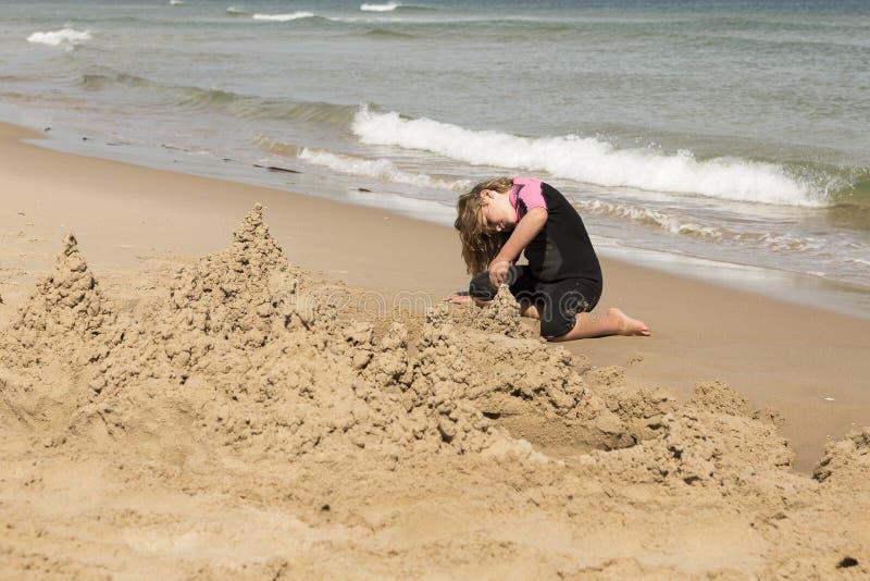 A menina no roupa de mergulho cor-de-rosa e preto que faz a areia fortifica imagens de stock royalty free