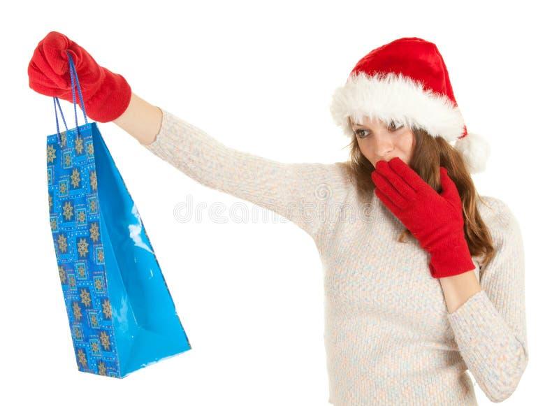 Menina no saco de compra carreg do chapéu de Santa imagens de stock royalty free