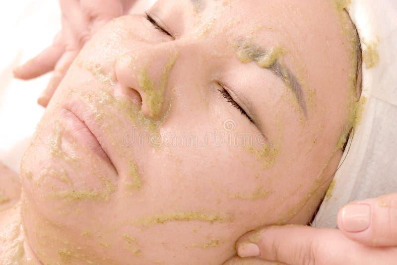 A menina no salão de beleza toma tratamentos faciais Close-up de uma mulher com uma máscara de algas verdes em sua cara Beleza e fotografia de stock royalty free