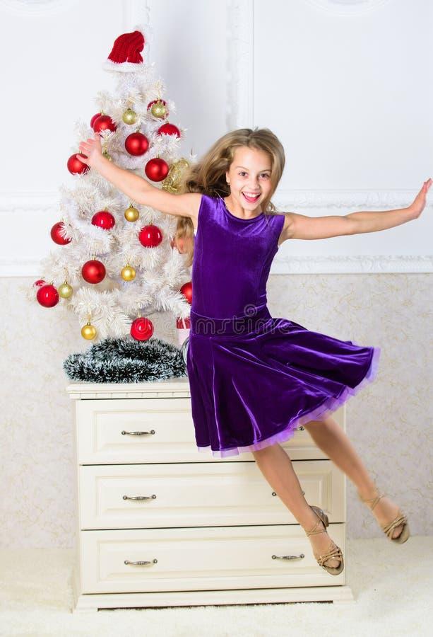 Menina no salto do vestido É Natal Dia onde nós esperamos todo o ano finalmente aqui Menina excitada sobre o salto do Natal foto de stock royalty free
