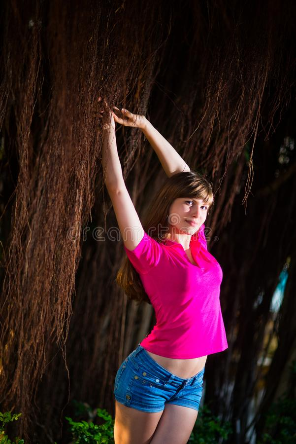 Menina no short da sarja de Nimes e na roupa cor-de-rosa que levantam com as videiras tropicais marrons imagem de stock royalty free