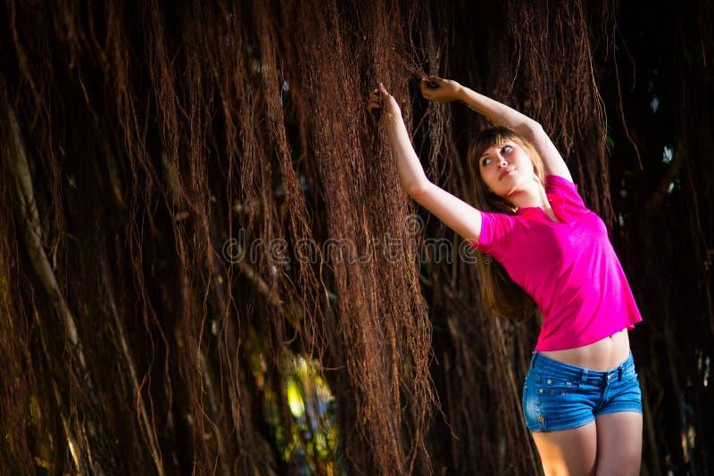 Menina no short da sarja de Nimes que levanta com as videiras tropicais marrons foto de stock royalty free
