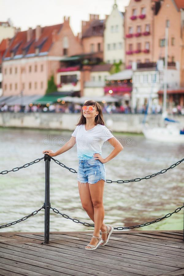 A menina no short de um t-shirt branco e da sarja de Nimes está estando no cais fotografia de stock royalty free