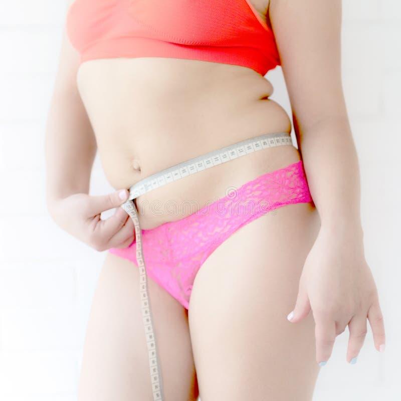 Menina no short e em um assunto mede o tamanho de seu centímetro do corpo fotos de stock