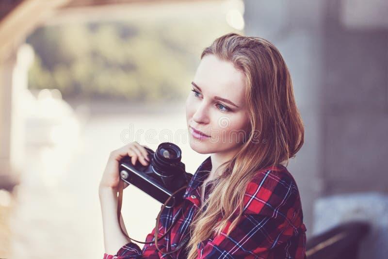 Menina no short e em uma camisa vermelha, com uma câmera retro imagem de stock