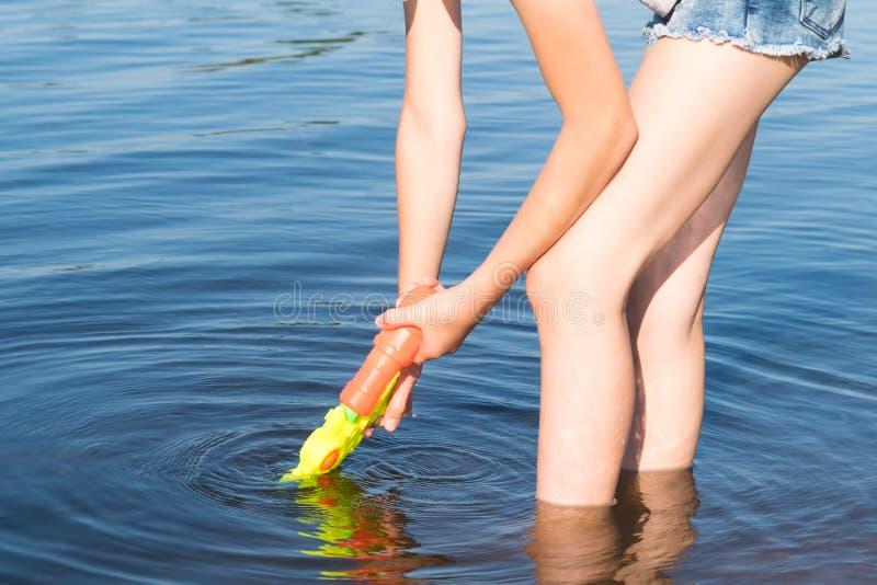 A menina no short está no rio e enche a pistola de água com água, close-up fotos de stock royalty free